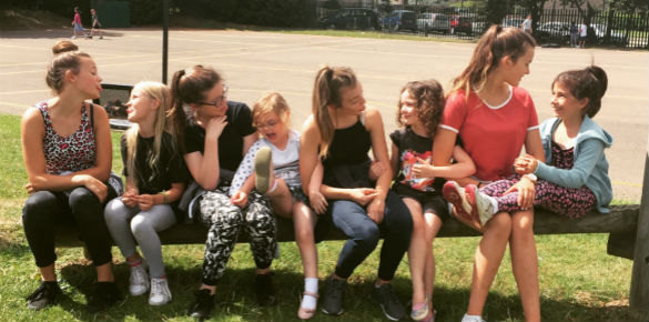 A line of girls sitting on a bench and looking at each other.