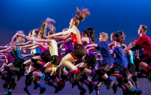 Side shot of a group and male and female dancers jumping in the air.