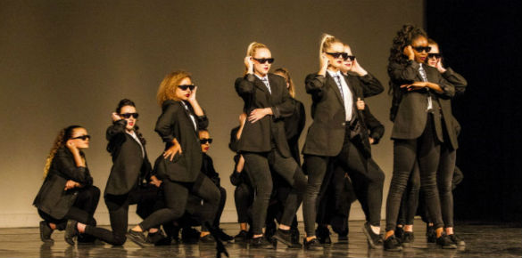 A group of female dancers in black suits, white shirts and dark glasses.