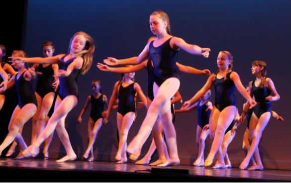A group of young, female ballet dancers in blue leotards dancing on stage.