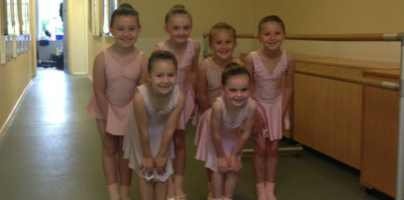 Six young ballet dancers standing together as they wait for their exam.