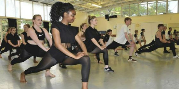 A group of teenage dancers in a studio lunging during a warm up.